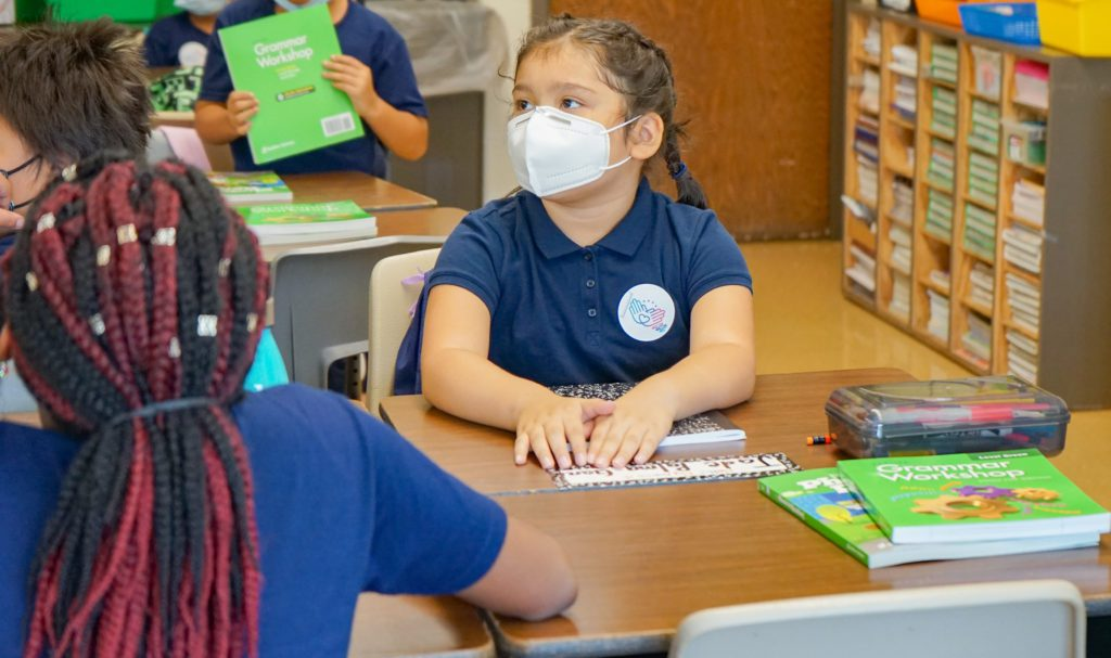 elementary student wearing mask sits at desk