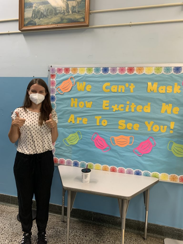 """person gives two thumbs up in front of poster reading """"we can't mask how excited we are to see you."""""""